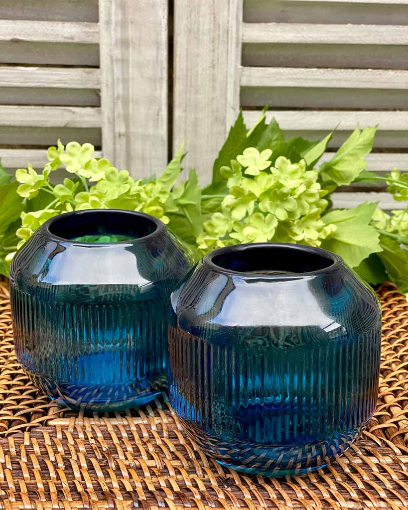 Two blue glass teal light holders, with ridged detailing pictured on rattan placemat.