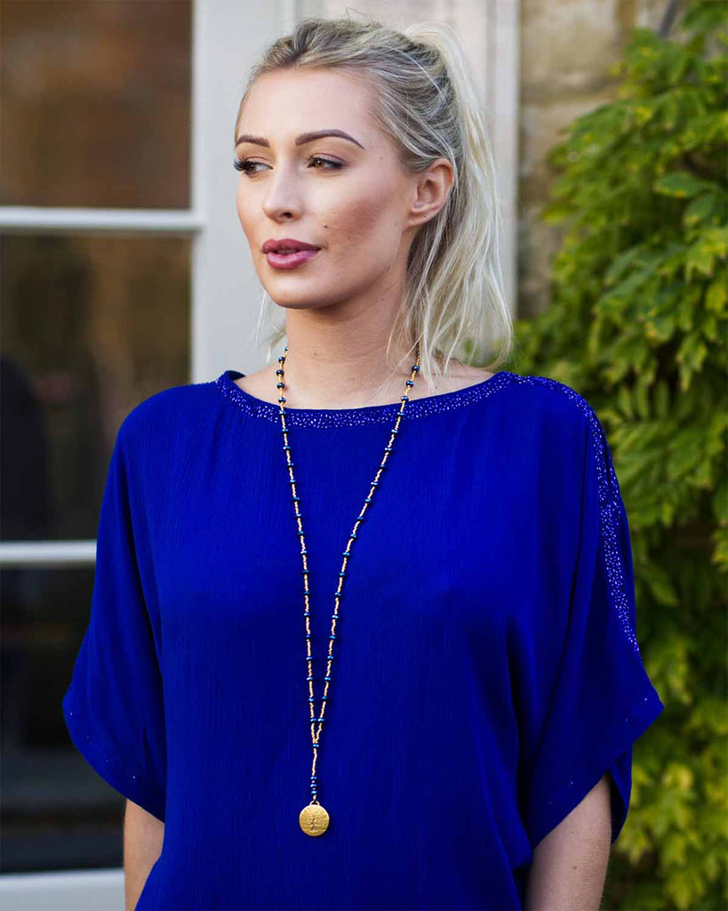Woman in cobalt blue top, outisde, wearing a cobalt crystal necklace with a tree of life pendant.