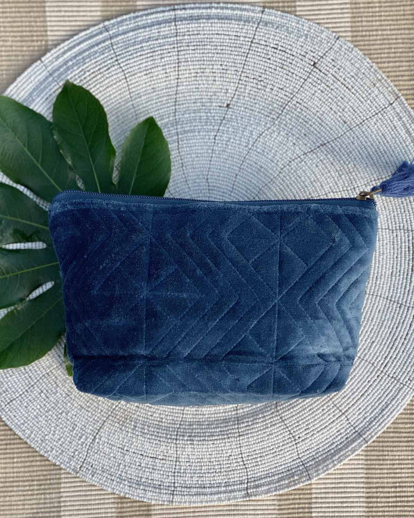Velvet navy pouch, inscribed with navy zig zags and a zip closure. On a placemat.