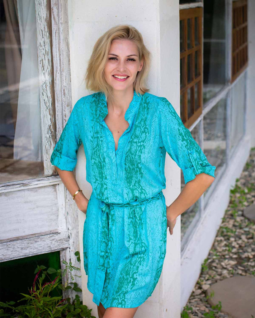 Woman in shirt style dress with tie waist belt, and 3/4 rolled sleeves. In a turquoise snake print