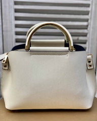 Small cream handbag with gold handles and gold strap attachments on gold stool.