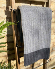 Dark grey cable throw hanging over a wooden ladder, edged with a dark grey stripe.