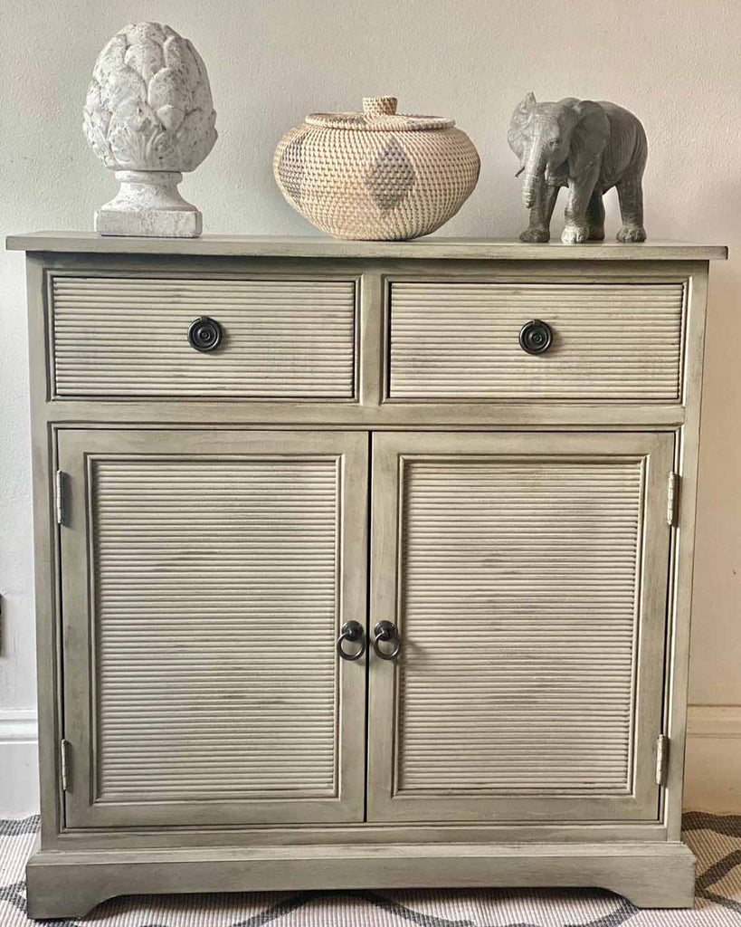 French style grey cabinet with two draws and one large cupboard with two shelves.