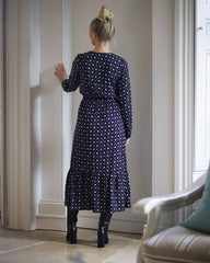 Back image of model posing in a black midi dress printed in a black batik print. It has an elasticated waist and elasticated sleeves. Model is wearing black leather boots on a beige tiled floor.
