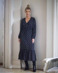 Model posing in a black midi dress printed in a black batik print. It has an elasticated waist and elasticated sleeves. Model is wearing black leather boots on a beige tiled floor.