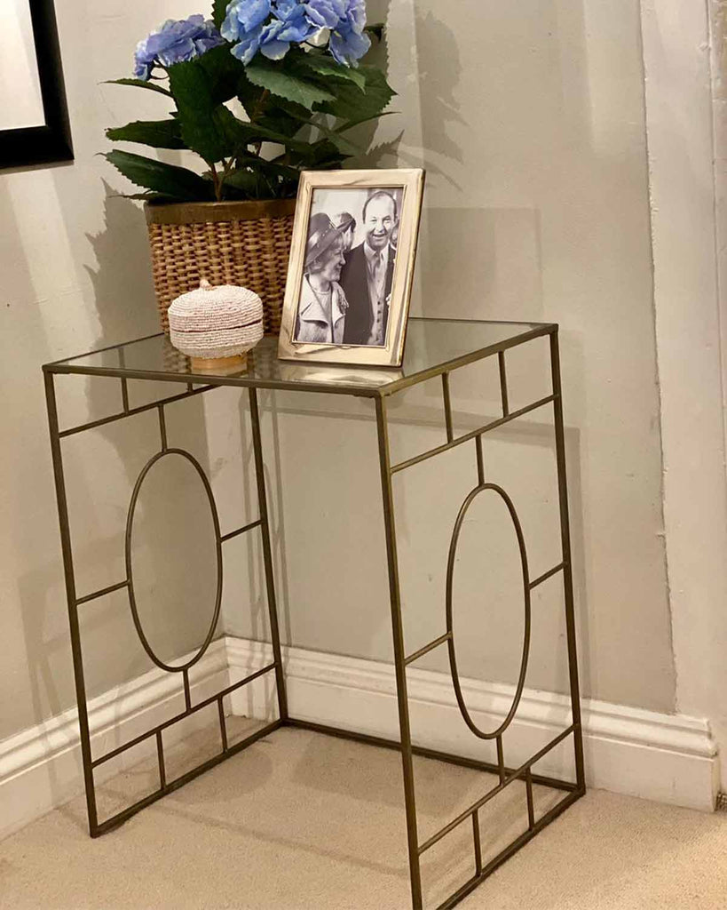 Metal structure side table with glass top.