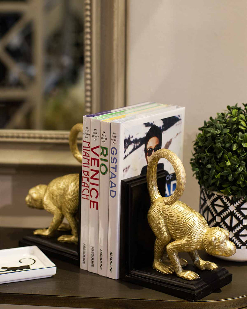Large gold monkeys on black wooden bookends.