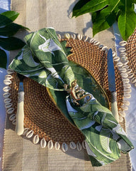 Banana leaf print napkin on rattan shell placemat with brass gecko napkin ring.