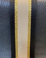 Close up image of black/beige/gold stripe bag strap.