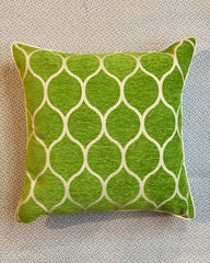 A cushion cover printed in moroccan green and white circle design.