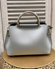 Light grey small handbag with gold handles and gold strap attachments on gold stool.