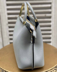 Side of light grey small handbag with gold handles and gold strap attachments on gold stool.