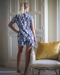 Behind image of woman in bedroom in grey leaf pjs with matching shirt style top and shorts.