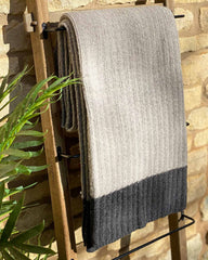 Light grey cable throw hanging over wooden ladder, it edged with a dark grey stripe.