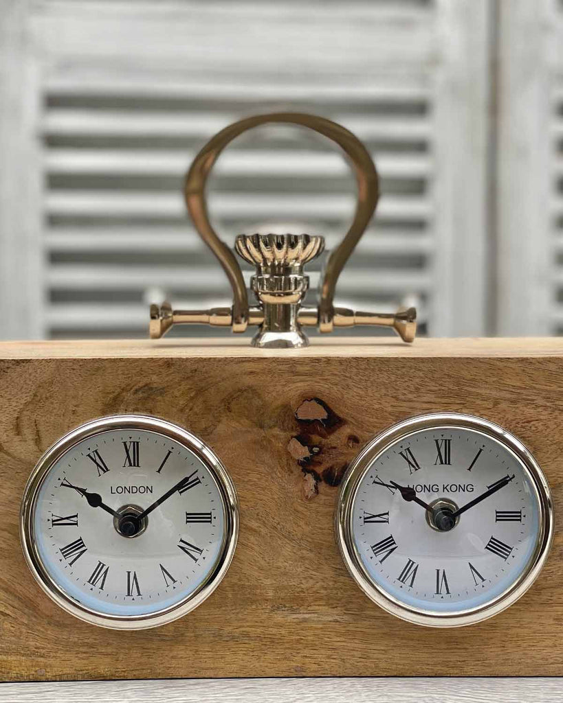 Wooden rectangular four face world clock with metal handle on top.