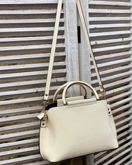 Small cream handbag with gold handles and long bag strap hanging from grey shutter.