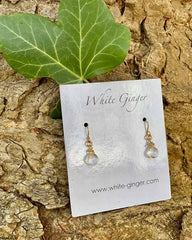 Pair of moonstone clear drop crystals, with gold clasps around the stones. On a white ginger earring board.
