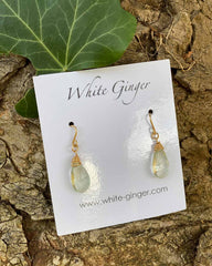 Pair of moonstone drop crystals, with gold clasps around the stones. On a white ginger earring board.