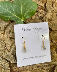 Pair of grey moonstone drop crystals, with gold clasps around the stones. On a white ginger earring board.