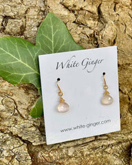 Pair of pink moonstone drop crystals, with gold clasps around the stones. On a white ginger earring board.