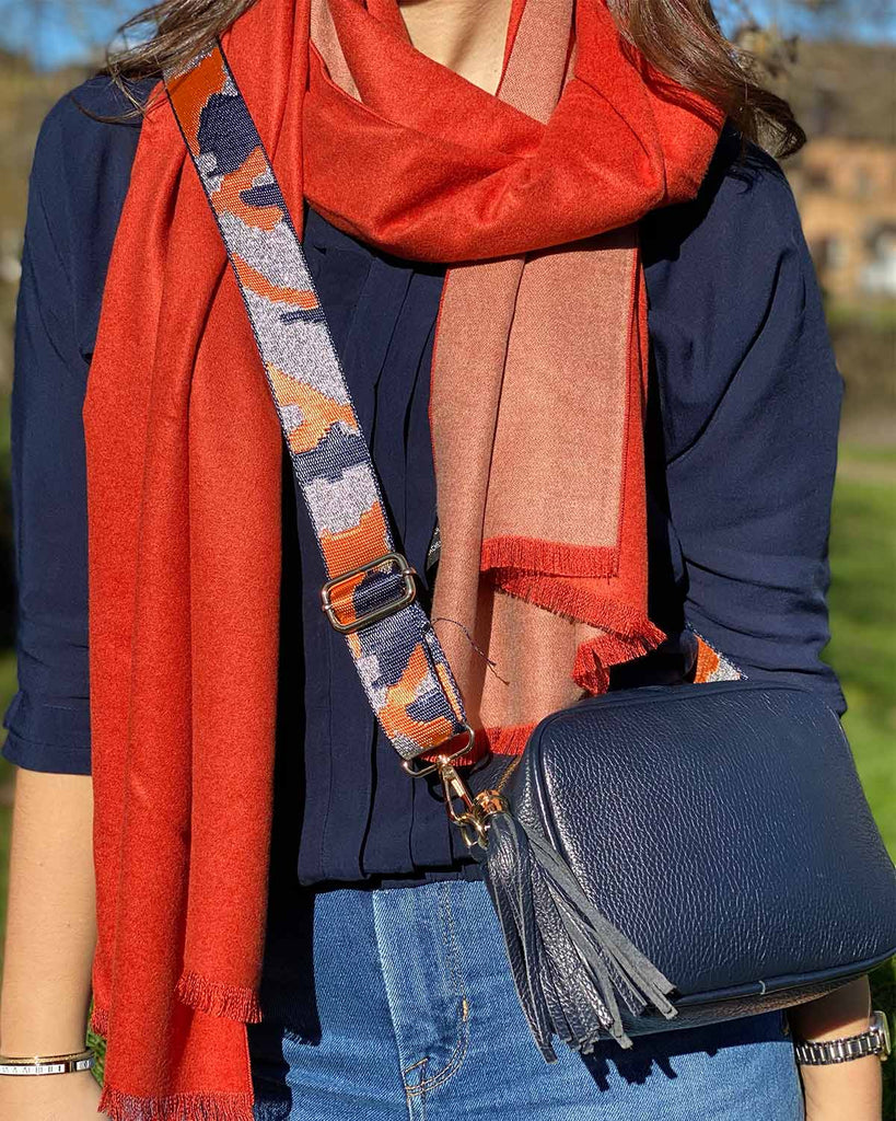 Woman wearing two tone camel and orange scarf with fringed bottom, navy tassel bag with camo/navy bag strap.