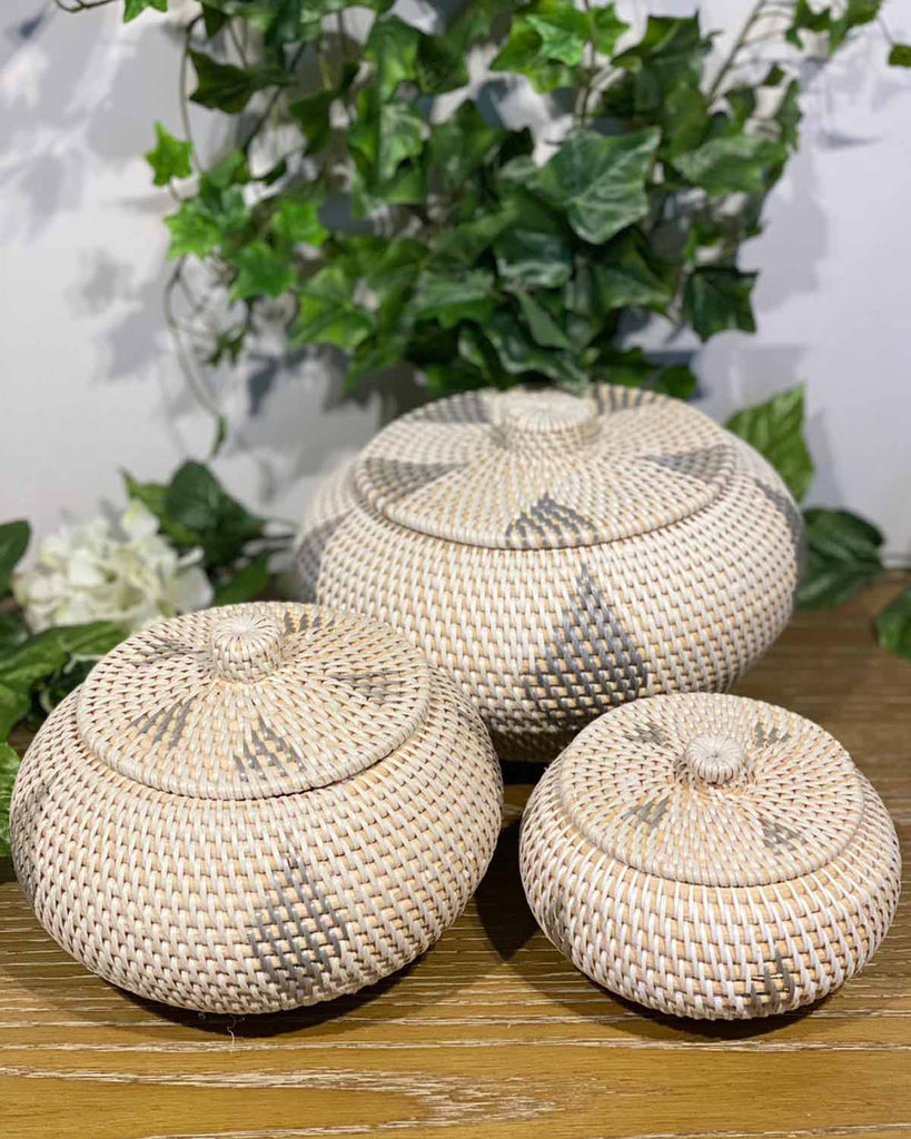 One small, one medium and one large white rattan oval pots with lids. They have a grey rattan pattern on the side and on top.