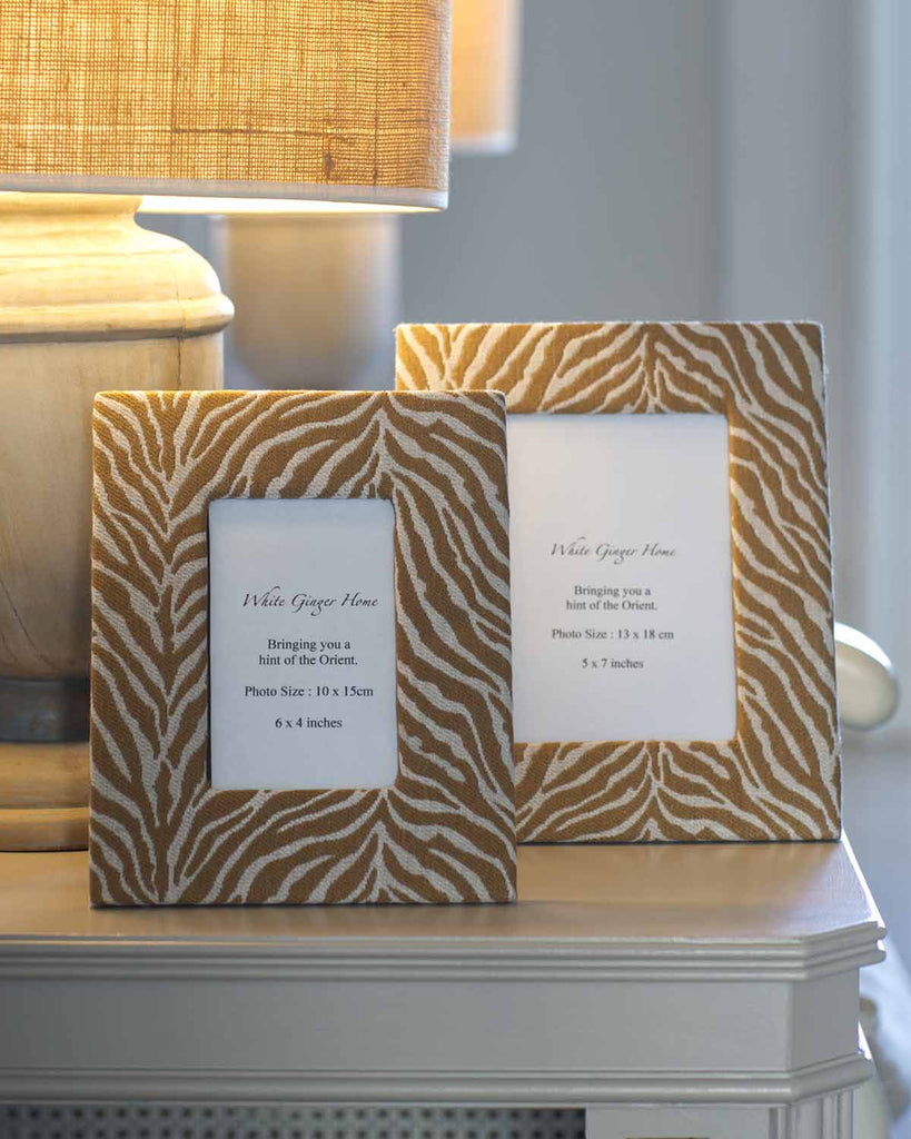 A small and a large photo frame printed in a beige animal print.