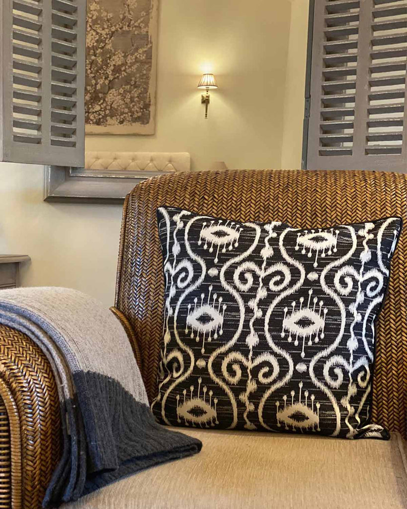 Black and white batik patterned cushion cover, pictured on rattan chair.