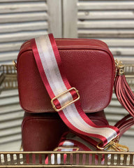 Red tassel bag with red/silver stripe bag strap going across it. On a mirrored table.