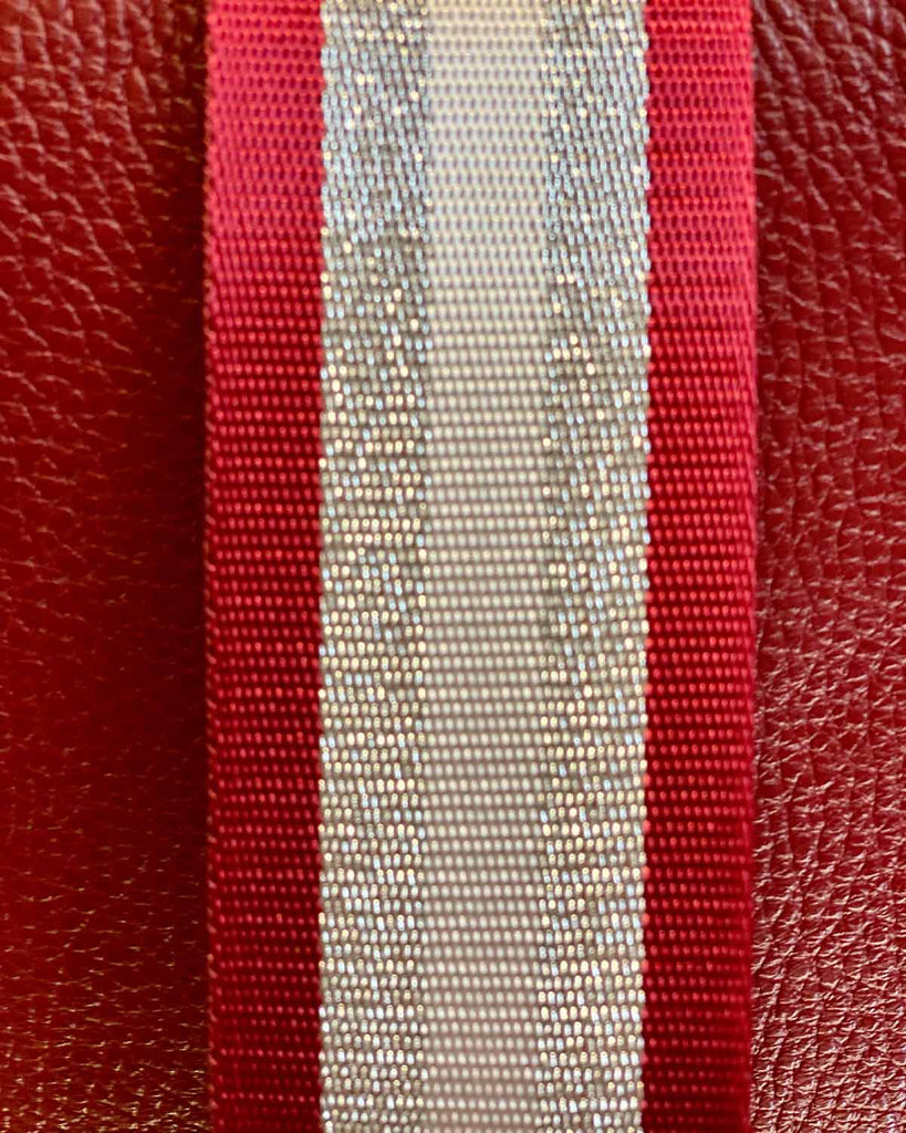 Close up image of red/silver stripe bag strap.
