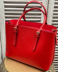 Red shopper bag with big handles on a gold side table.