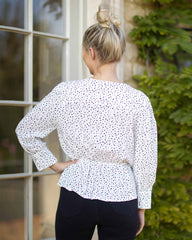 Back pose of a woman by a terrace door wearing a black dotted print on white. With a elasticated waist and cross over neck line.