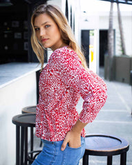 Side image of woman in red and white tiger printed top, with a cross over design at the front and elasticated waist.