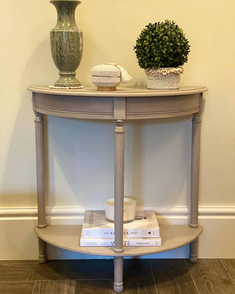 Grey wooden half moon side table with one shelf at the top and one shelf at the bottom.