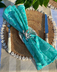 Turquoise seashell print napkin on rattan shell placemat with silver gecko napkin ring.