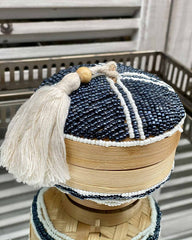 Wooden pot with a beaded top and bottom, with a white bead pattern and tassel on top.