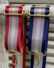 Two bag straps showing attachments, one with red/silver stripe and one with navy/silver stripe.