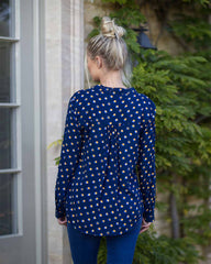 Behind image of woman outside in a navy blouse, printed with a orange poka dot and wearing blue jeans.