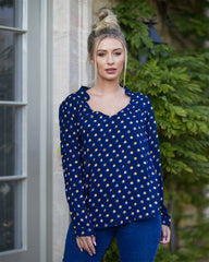 Woman outside in a navy blouse, printed with a orange poka dot and wearing blue jeans.