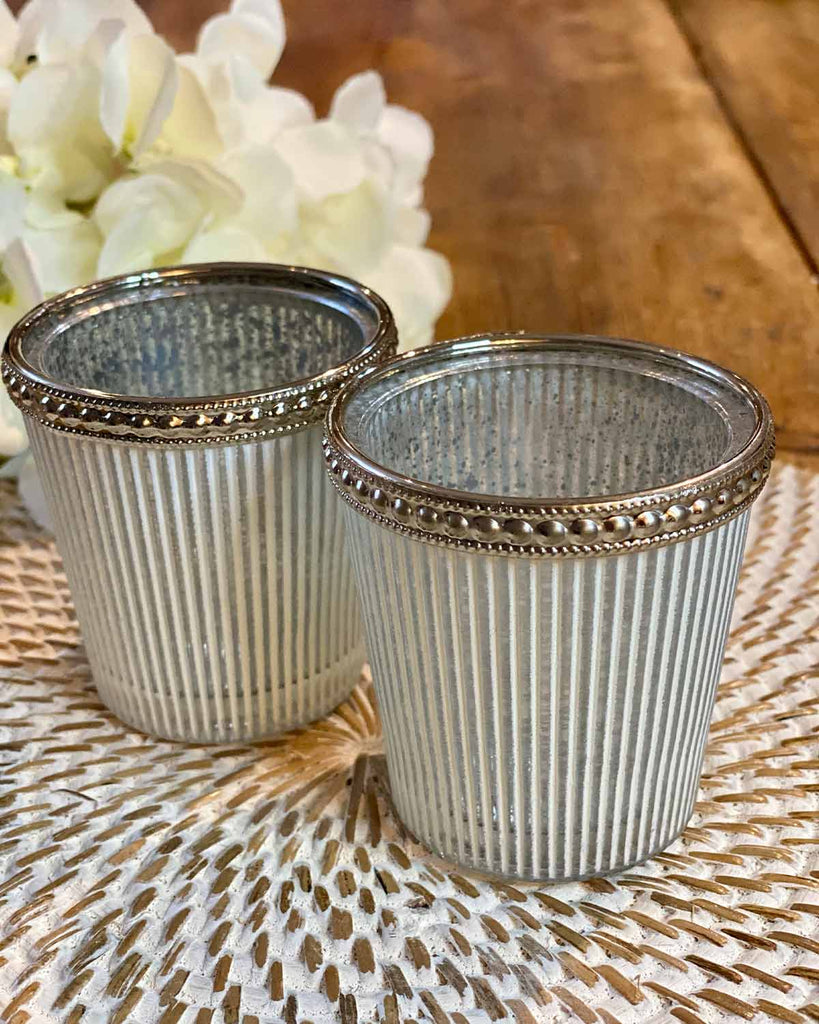 Two white and grey striped tea lights, edged in silver at the top.