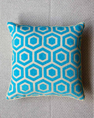 Close up of cushion cover in turquoise and cream geometric print.