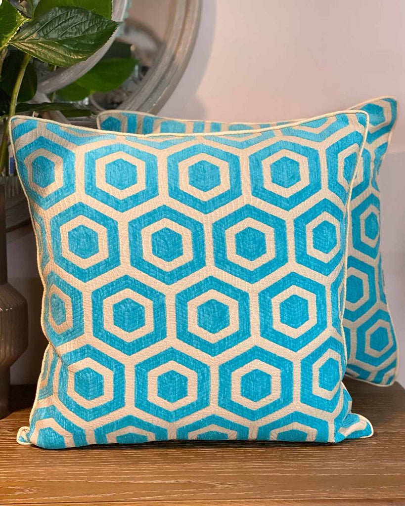 Two large cushion covers in turquoise and cream geometric print.