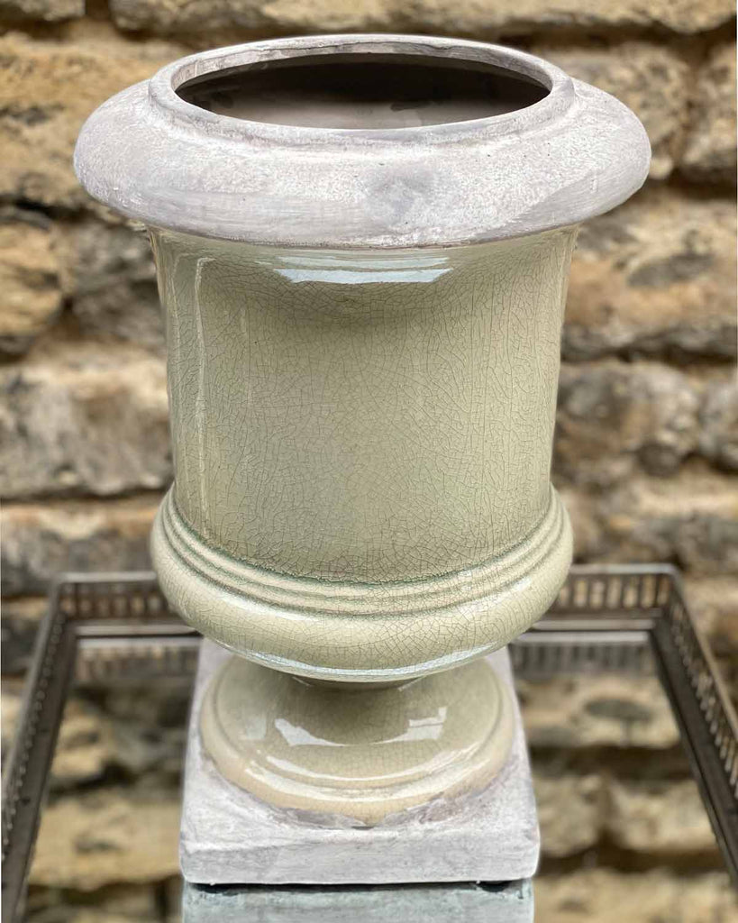 Large light grey stone urn with faux hydrangeas in.