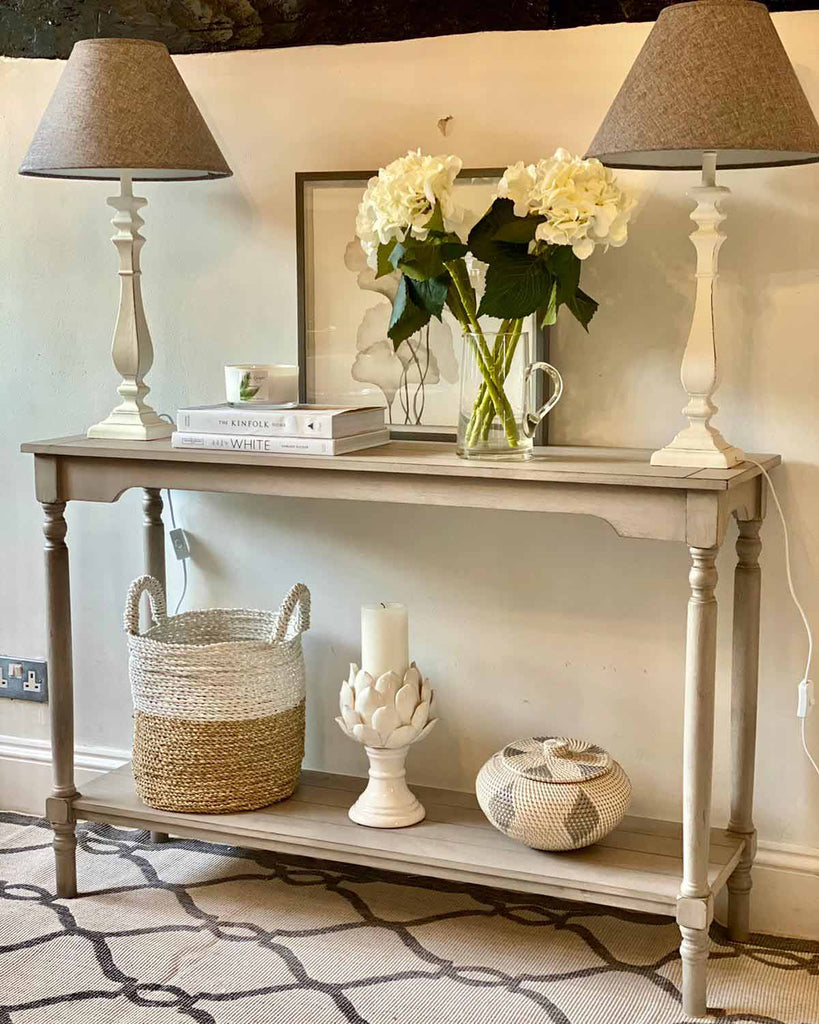 Two french style wooden cream table lamp with a dark grey shade. Pictured on cream console table.