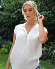 Woman outside wearing a short sleeved blouse, coloured with winter white.