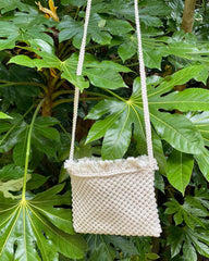 A cream square woven charity cross body bag, hanging on a green bush.