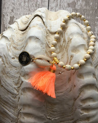 Bali tassel bracelet with beads, a shell and coral tassel.