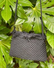 A black square woven charity cross body bag, hanging on a green bush.