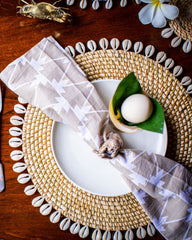 Natural placemat edged with shells, pictured with plate and napkin.