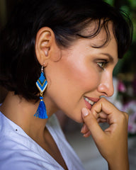 Woman smiling with cobalt and white beaded earrings with a cobalt tassel.